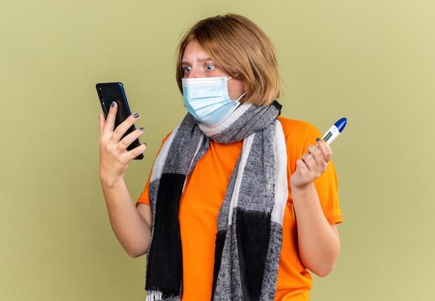 Giovane donna malsana con sciarpa calda intorno al collo che indossa la maschera protettiva facciale che soffre di raffreddore e influenza che tiene il termometro parlando al telefono cellulare guardando preoccupato sulla parete verde