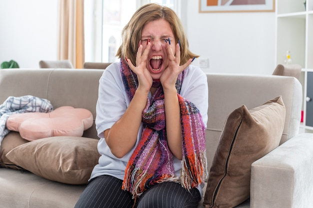 Unhealthy young woman with warm scarf around neck feeling terrible suffering from virus shouting in panic sitting on couch in light living room