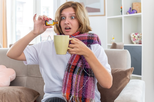 首に暖かいスカーフを巻いた不健康な若い女性が、インフルエンザや風邪の滴り落ちる薬に苦しんで気分が悪く、明るいリビングルームのソファに座っているカップに落ちる