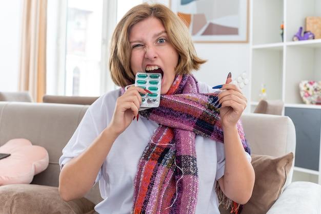 Нездоровая молодая женщина с теплым шарфом на шее чувствует себя нездоровой и больной, страдает от гриппа и простуды, держит в руках разные таблетки, кусая волдырь, выглядит смущенным, сидя на диване в светлой гостиной