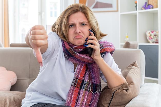 목 주위에 따뜻한 스카프가있는 건강에 해로운 젊은 여성은 가벼운 거실에서 소파에 앉아 tumbs를 보여주는 휴대 전화로 독감과 감기로 고통 받고 아픈 느낌