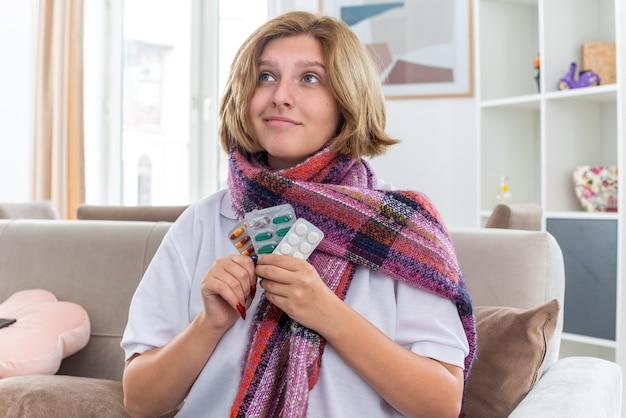 Giovane donna malsana con sciarpa calda intorno al collo che tiene diverse pillole alzando lo sguardo con un sorriso sul viso sentendosi meglio seduta sul divano in un soggiorno luminoso