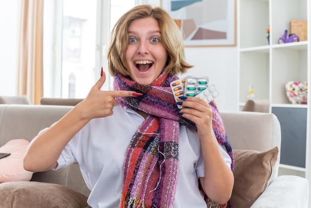 검지 손가락으로 가리키는 다른 약을 들고 목 주위에 따뜻한 스카프로 건강에 해로운 젊은 여성이 밝은 거실에서 소파에 앉아 기분이 좋게 웃고 있습니다.