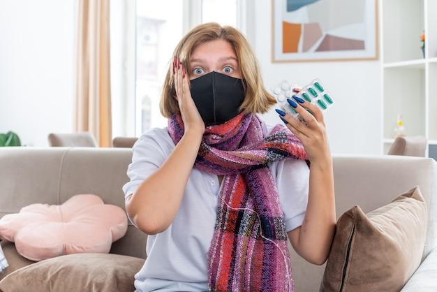 밝은 거실에서 소파에 앉아 혼란스러워 보이는 독감과 감기에 걸린 약을 앓고있는 얼굴 보호 마스크가있는 목 주위에 따뜻한 스카프가있는 건강에 해로운 젊은 여성