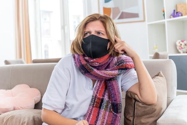 暖かいスカーフを首に巻いた不健康な若い女性で、顔の保護マスクが気分が悪く、インフルエンザにかかって病気になり、明るいリビングルームのソファに寒そうに見えて混乱している