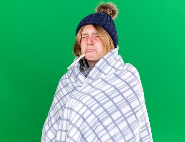 Giovane donna malsana avvolta in una coperta che indossa un cappello che misura la sua temperatura corporea usando un termometro che si sente male soffre di influenza avendo la febbre in piedi sul muro verde