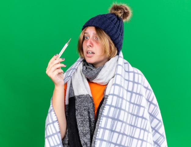 Giovane donna malsana avvolta in una coperta che indossa un cappello che misura la sua temperatura corporea usando un termometro che soffre di influenza con febbre che sembra preoccupata in piedi sul muro verde green
