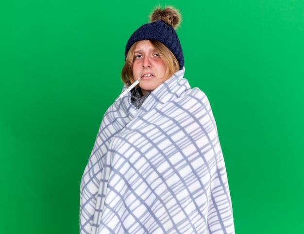 Giovane donna malsana avvolta in una coperta che indossa un cappello che misura la sua temperatura corporea usando un termometro che soffre di influenza con febbre in piedi sul muro verde