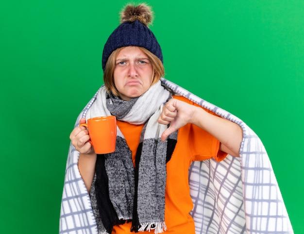 Нездоровая молодая женщина, завернутая в одеяло, в шляпе и шарфе, пьет горячий чай, страдает от холода, чувствуя тошноту, показывает палец вниз, стоя у зеленой стены