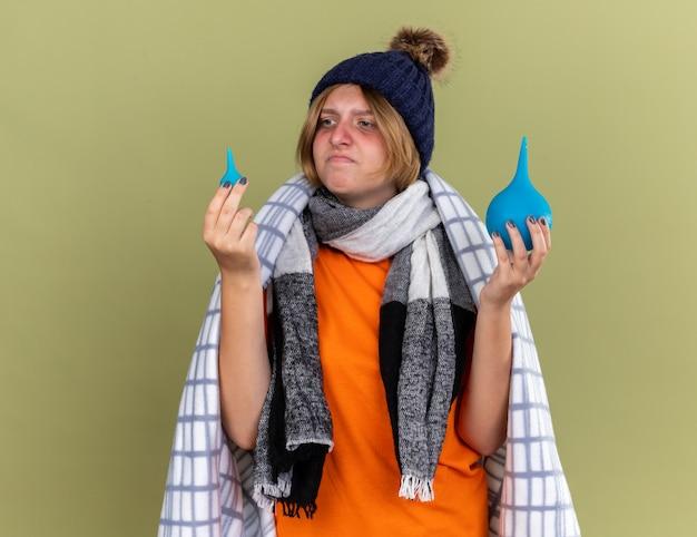 건강에 해로운 젊은 여성이 모자와 스카프를 착용하고 녹색 벽 위에 서서 혼란스럽고 불쾌한 느낌을주는 관장을 들고 기분이 좋지 않은 담요에 싸여 있습니다.