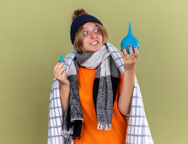 건강에 해로운 젊은 여성이 모자와 스카프를 착용하고 관장기를 들고 담요에 싸여 녹색 벽 위에 서있는 기분이 좋지 않습니다.