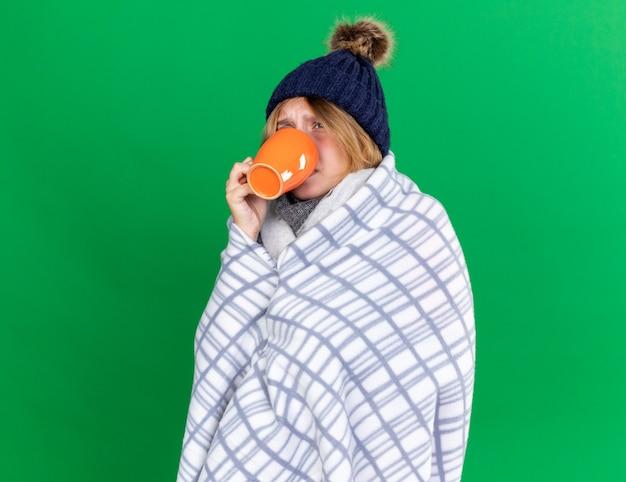 건강에 해로운 젊은 여성이 모자를 쓰고 담요에 싸여 차가운 느낌으로 고통받는 뜨거운 차를 마시고 있습니다.