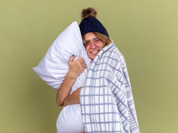 감기와 독감으로 고통받는 베개를 들고 모자를 쓰고 담요에 싸여 건강에 해로운 젊은 여성이 녹색 벽 위에 서서 아프고 짜증이납니다.