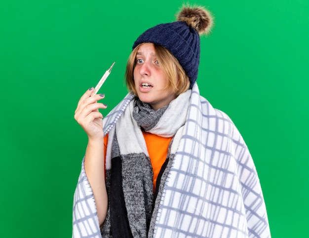 건강에 해로운 젊은 여성이 독감으로 고통받는 온도계를 사용하여 그녀의 체온을 측정하는 모자를 쓰고 담요에 싸여 녹색 벽 위에 서있는 걱정을 찾고 있습니다.