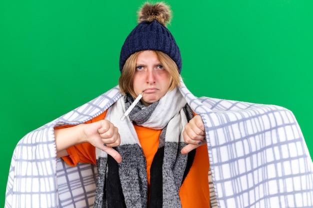 帽子をかぶった毛布に包まれた不健康な若い女性が、インフルエンザにかかっている体温計を使って体温を測り、発熱を起こし、緑の壁の上に親指を下に向けて立っている