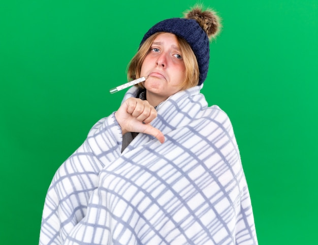 건강에 해로운 젊은 여성이 녹색 벽 위에 서 엄지 손가락을 보여주는 독감으로 고통받는 온도계를 사용하여 그녀의 체온을 측정하는 모자를 쓰고 담요에 싸여 있습니다.