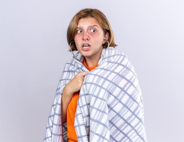 건강에 해로운 젊은 여성이 걱정하고 무서워 보이는 청진기를 사용하여 그녀의 심장 박동을 듣고 아픈 느낌이 든 따뜻한 담요에 싸여 있습니다.