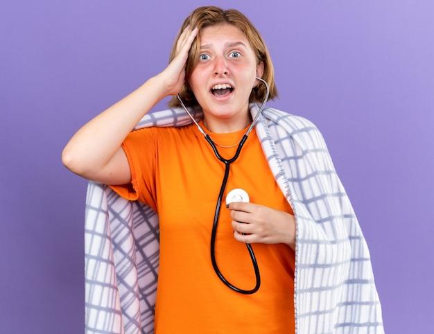 Giovane donna malsana avvolta in una coperta calda che si sente male ascoltando il suo battito cardiaco usando lo stetoscopio che sembra preoccupata e spaventata