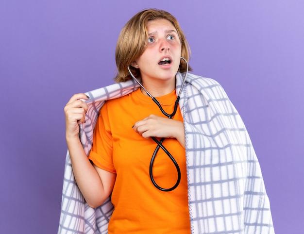 Giovane donna malsana avvolta in una coperta calda che si sente male ascoltando il suo battito cardiaco usando lo stetoscopio che sembra preoccupata in piedi sul muro viola