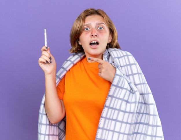 Giovane donna malsana avvolta in una coperta calda che si sente male soffre di influenza avendo la febbre che misura la sua temperatura usando un termometro che lo punta guardando preoccupata in piedi sul muro viola