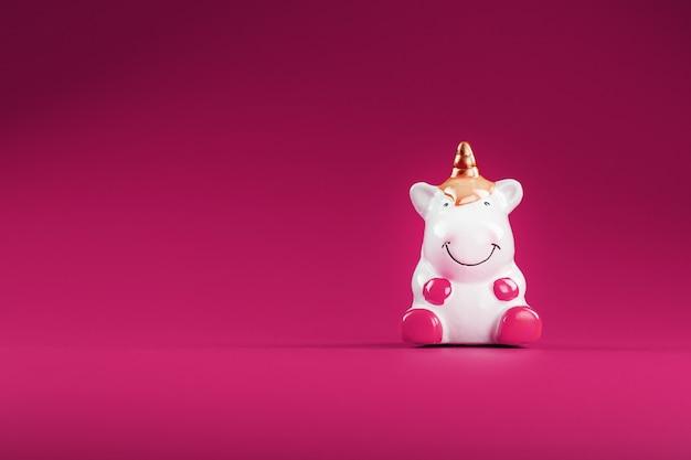 Фигурка единорога на розовом фоне. свободное место
