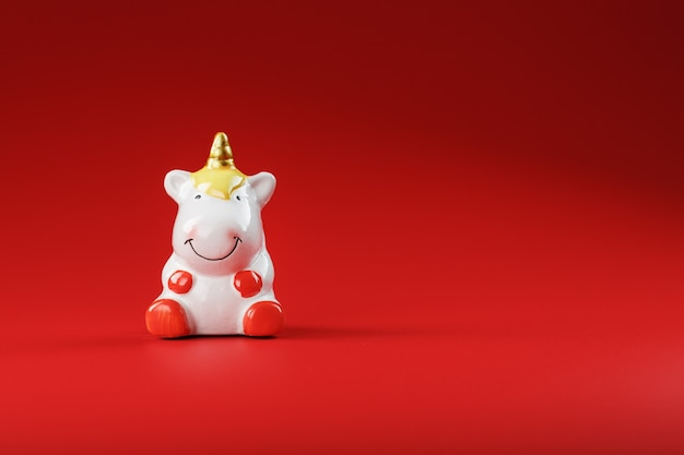 Unicorn figurine on a red background with free space