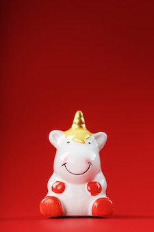 Unicorn figurine on a red background with free space.