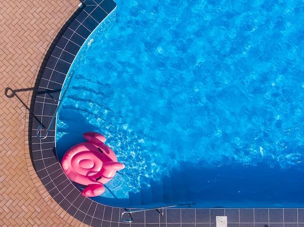 유니콘 플라밍고는 푸른 물 배경에 떠 있고, 부풀릴 수 있는 수영 튜브