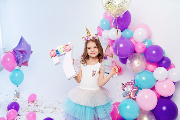 Unicorn girl holding gold confetti air baloon and letter 7. idea for decorating unicorn style birthday party. unicorn decoration for festival party girl