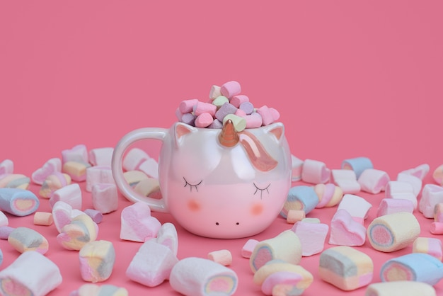 Unicorn mug with multi-colored marshmallows scattered around on a pink background. sweets concept with place for text.