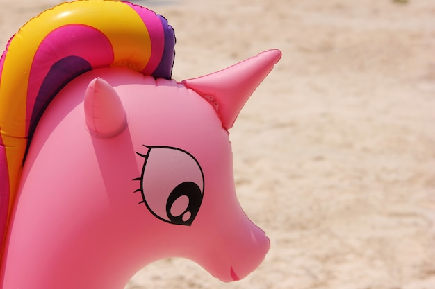 The unicorn's head from the pink water wings closeup. summer holidays and the beach.