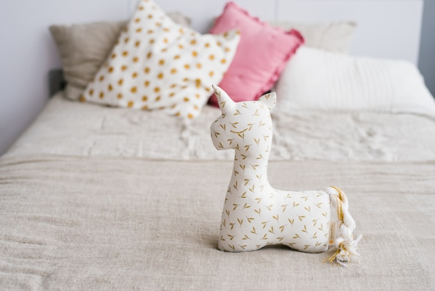 Unicorn soft toy on the bed on the background of multi-colored pillows