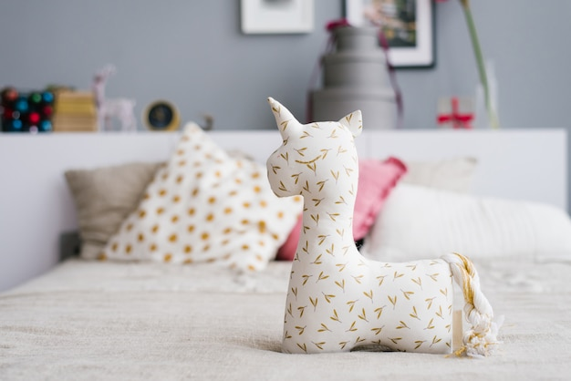 Unicorn soft toy for children on the bed in the bedroom