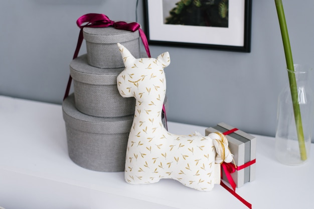 Unicorn soft toy for children and three round gift boxes tied with burgundy ribbon