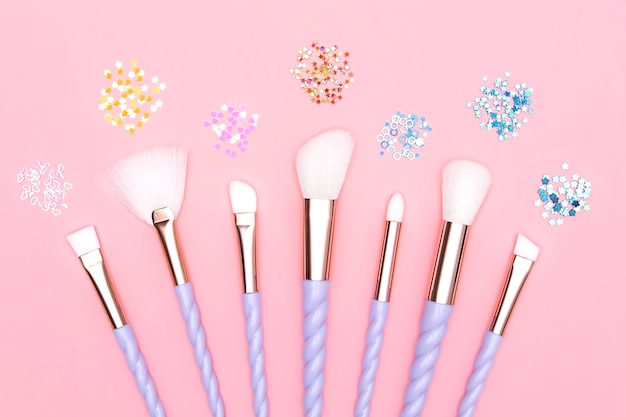 Unicorn violet and white make-up brush set collection kit with multi colored glitter shimmer isolated on pink background. copy space. stage make-up concept, beauty products, female face care accessory