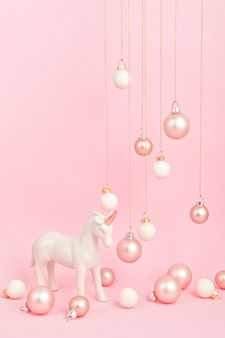 Unicorn with christmas ornaments over pink surface