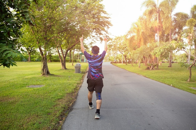 Unidendified man winner celebrating sport success raising hands up.