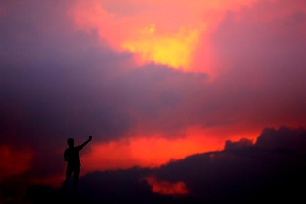 Неизвестные люди, стоящие на вершине, глядя на многоцветный абстрактный фон