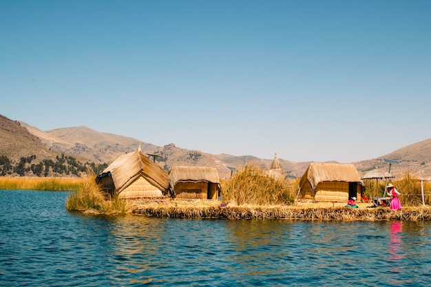 Unidentifiable local women working in lake titicaca uros community, peru