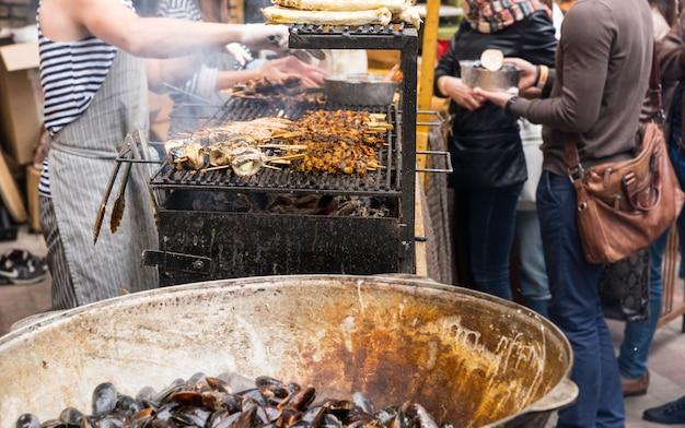 Неизвестные люди готовят мясные шашлычки над курением горячего гриля-барбекю и обслуживают клиентов на фестивале еды