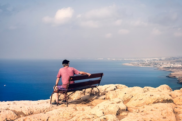Unidentified adult male sitting on a bench and enjoy the view of the mountains, city in the distance and the bay. lonely old man. concept of loss, sorrows and loneliness