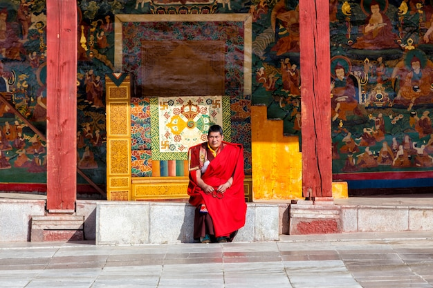 Unidentified buddhist monks smiling are praying in boudhanath monastery, sichuan, china