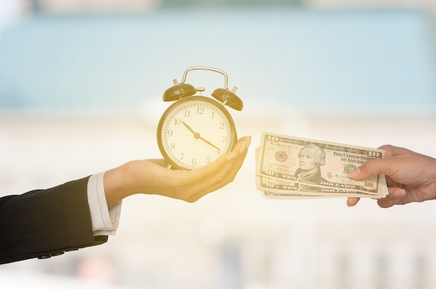 Unidentified business people hands show black alarm clock and dollar bank note