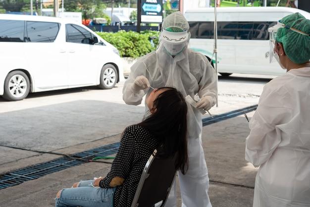 Неизвестный врач в костюме сиз и азиатский пациент проверяют образец covid-19, выполняя мазок из носоглотки или ротоглотки из носа и полости рта в больнице