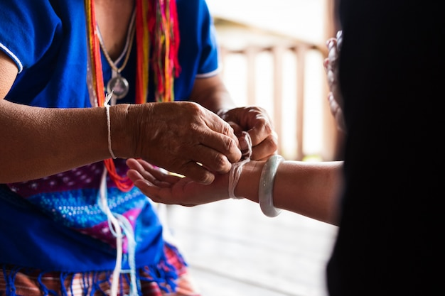 Unidentified elder woman from karen ethnic hill tribe minority tie guest's wrist for blessing in tying ceremony