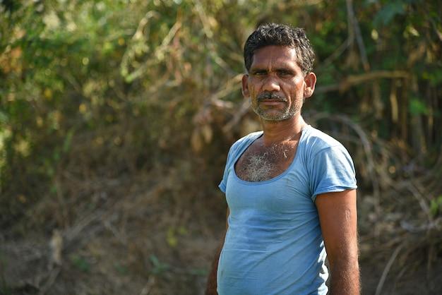 正体不明のインドの農場労働者が畑にキャベツを植え、有機農場でキャベツの小さな植物の束を手に持っています。