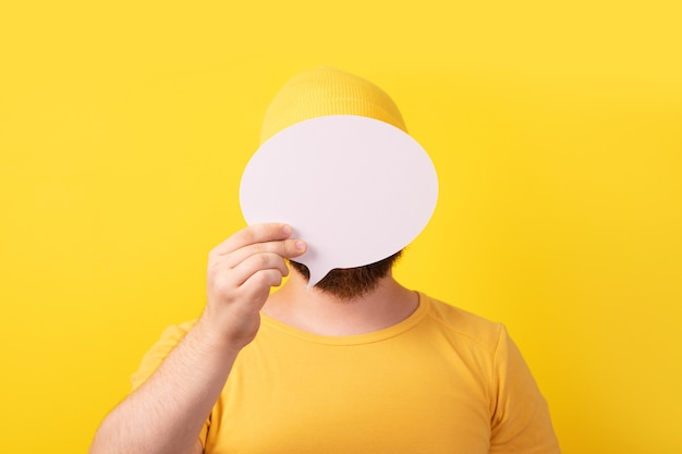 Unidentified man holding speech bubble with empty space for text over yellow background