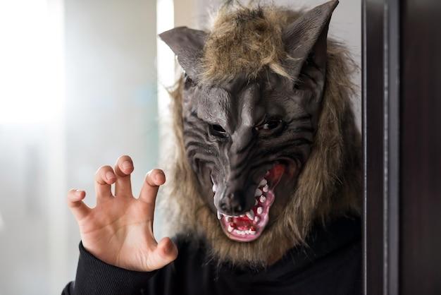 늑대 마스크와 검은 드레스 의상을 입은 신원 미상의 남자가 창문에서 빛이 들어오는 어두운 방에 있습니다. 2021년 할로윈 파티 컨셉을 위한 무서운 모델입니다.