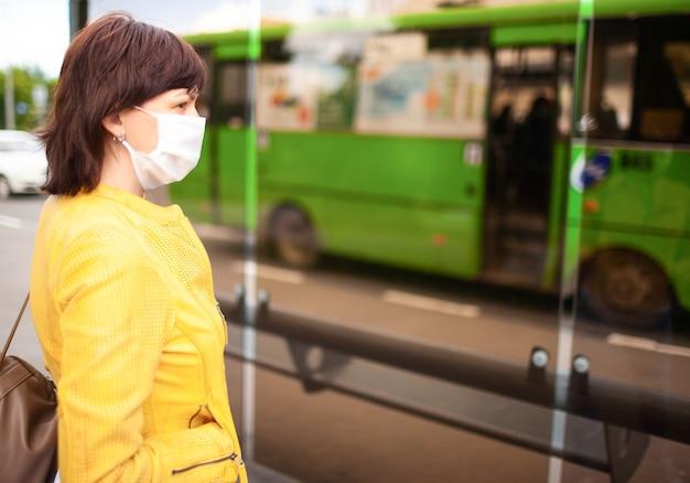 スタイリッシュなカジュアルウェアを着た正体不明の中年女性が白い医療包帯のバス停でバスを待っています