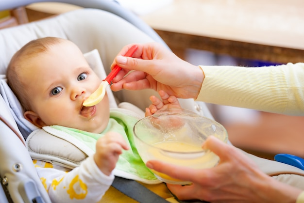 Unidentified mothers hand carefully feeds a cute healthy newborn girl with baby food.
